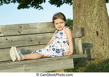 Happy cute little girl sitting on a bench