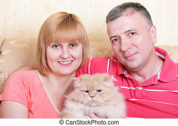 A happy family enjoying their free time at home with fluffy ...
