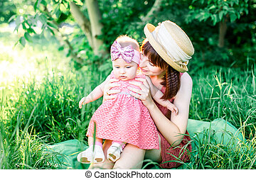 A happy family having a picnic in the green garden in a sunny spring day: a beautiful smiling mother sitting on green grass and her little laughing daughter on her legs.