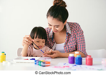 A happy family is painting. Mom help her daughter drawing