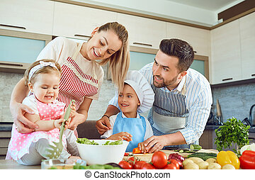 A happy family is preparing in the kitchen.