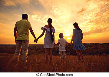 A happy family is standing in the nature at sunset in the evenin