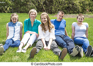 Happy family members sitting in green grass outdoors