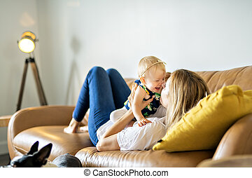 happy family. Mother and baby daughter plays, on the sofa