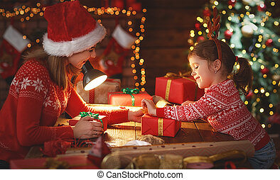 happy family mother and child pack Christmas gifts