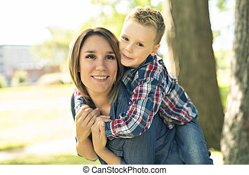 happy family mother and child son playing on autumn park