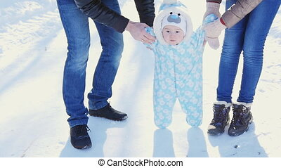 A happy family. Mother and father teaches a child to walk in winter park