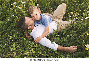 happy family of father and child on field at the sunset having fun lay together