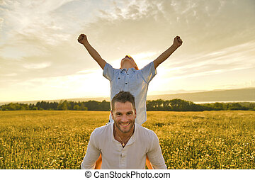 happy family of father and child on field at the sunset having fun on back with hand high