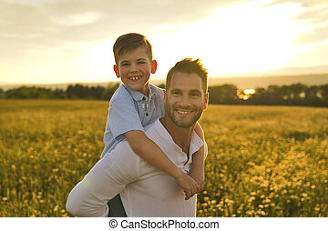 happy family of father and child on field at the sunset having fun