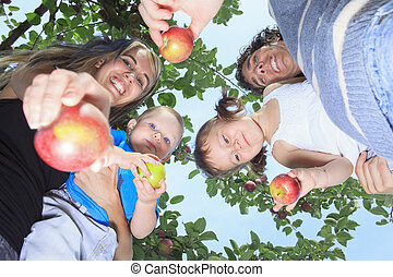 A happy family of four attractive caucasian catch apple