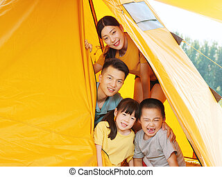 A Happy family of four in tent
