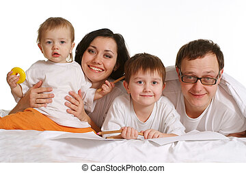 A happy family of four people lying