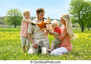 a happy family of four people, mother, father, young child and toddler, are playing with stuffed fox toys outside in a Dandelion flower meadow on a Spring day.