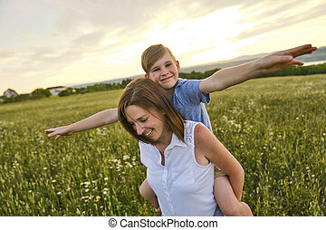happy family of mother and child on field at the sunset having fun
