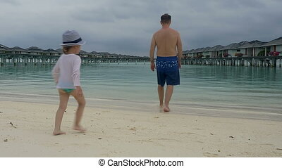 A happy family of three relax on a tropical beach in...