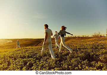 A happy family runs across the field at sunset.