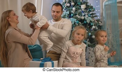 A happy family sitting by the New Year tree, parents are playing with children, smiling and laughing