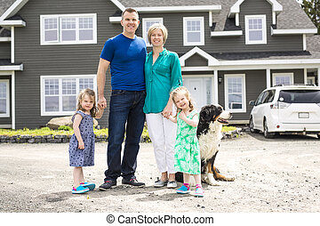 happy family standing in front of the house