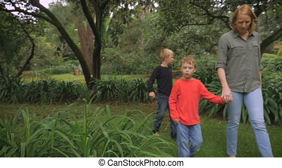 A happy family walking together in a park holding hands -...