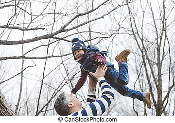 happy father and son having fun in park at the end of october
