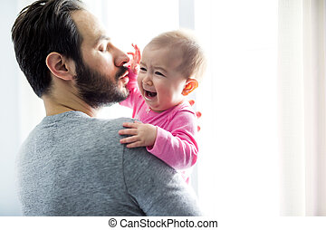 happy father playing with adorable baby in bedroom