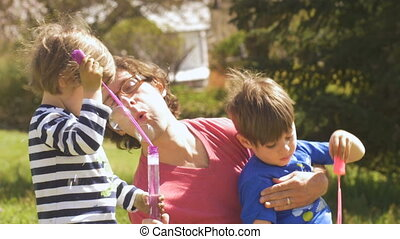 A happy father with his two children blowing bubbles and...