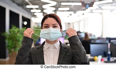 A happy female office worker in a suit takes off medical mask. A smiling woman takes off her virus protection. End of quarantine. Victory over the coronavirus