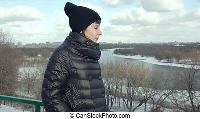 A happy girl is walking in a winter park. Slow motion.