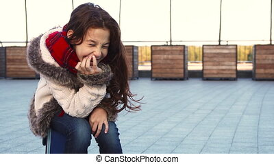 A happy girl laughs hard while sitting on the street