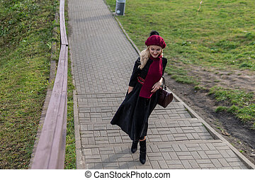 A happy girl walks up the stairs in a burgundy palette and biret, with a charismatic appearance in black clothes, in the fall against a blue sky.