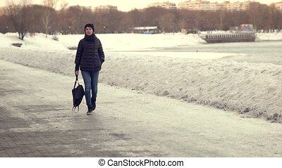A happy girl with a backpack in hand is walking in a winter park. Slow motion.