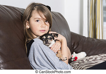 Happy girl with his dog on sofa