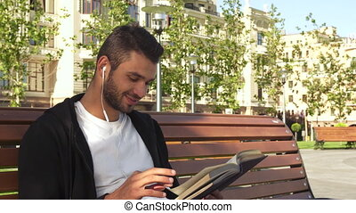 A happy guy is reading a book in a city alley
