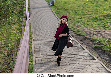 A happy lady is walking up the stairs, both in burgundy palette and biret, an adult with beautiful eyes in black clothes, in the fall against a background of blue clouds.