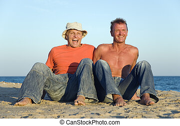A happy laughing gay couple on beac