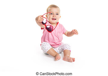 happy little baby girl in bright pink dress isolated on a white background