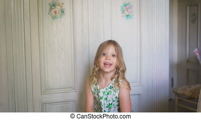Happiness. Careless childhood. A happy little girl in the dress is jumping in the bright room. A little blondie is jumping and turning around in the bright room.