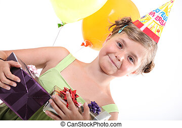 a happy little girl with her birthday gifts