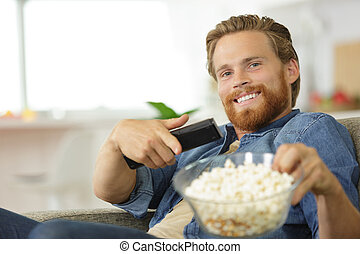 a happy man eating popcorn