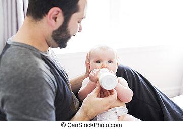 Happy man feeding milk to baby girl at home