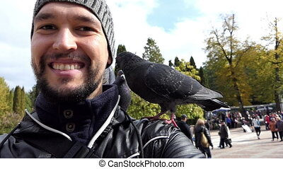A happy man has a dove on his shoulder on a square in slo-mo