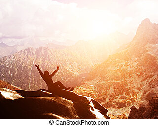 A happy man sitting on the peak of a mountain with hands raised at sunset