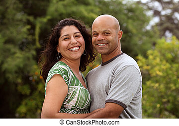 A happy mixed race couple relax outside in the back yard or...