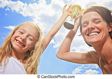 Happy mother and daughter holding a trophy high up - A Happy...