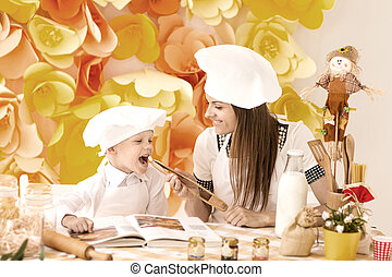 A happy mother and her child in the form of cooks prepare a delicious lunch