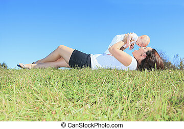 A Happy mother and her little son in the summer field