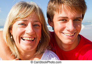mother and teen son - a happy mother and teen son smiling on...