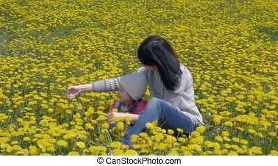 A happy mother makes a selfie, a photo with her little daughter on the field with yellow dandelions. Family walking in the city park. Slow motion