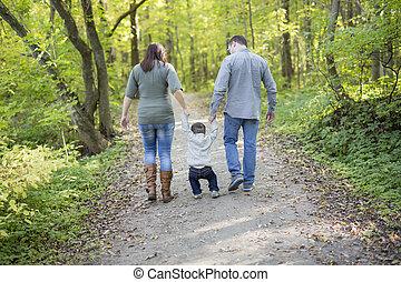 Happy pregnant family having fun in autumn nature
